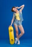 Mulher alegre que está com skate foto de stock
