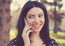 Mulher alegre que fala em um telefone fora fotografia de stock royalty free