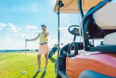 Mulher alegre que fala no telefone celular no campo de golfe fotografia de stock royalty free