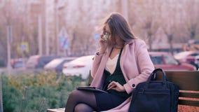 Mulher alegre que fala no telefone e que usa a tabuleta ao sentar-se no banco na cidade video estoque
