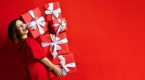 Mulher alegre que guarda muitas caixas com presentes foto de stock