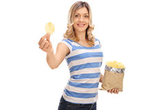 Mulher alegre que guarda um saco das microplaquetas fotografia de stock