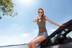 Mulher alegre que inclina-se no carro Fotos de Stock