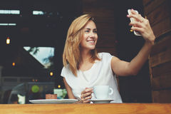 Mulher alegre que levanta ao fotografar-se para a imagem social da rede, espaço da cópia fotografia de stock