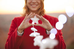 Mulher alegre que mantém a decoração do Natal das estrelas iluminada Imagens de Stock Royalty Free