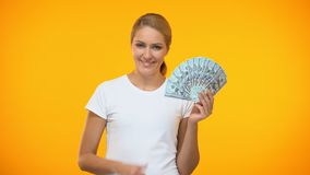 Mulher alegre que mostra os polegares acima de guardar dólares à disposição, bem trabalho pago, lucro video estoque