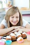 Mulher alegre que olha bolos na cozinha Imagens de Stock