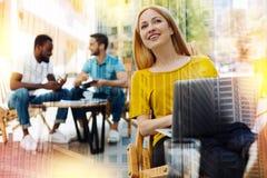 Mulher alegre que senta-se com um portátil e que sorri ao ver seu amigo Imagens de Stock Royalty Free