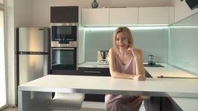 Mulher alegre que senta-se na tabela na cozinha video estoque