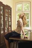 Mulher alegre que senta-se na tabela do estudo em casa fotografia de stock