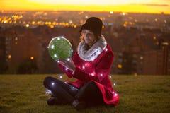 Mulher alegre que senta-se no assoalho que guarda fora um balão w Fotos de Stock