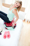 Mulher alegre que tenta fechar sua mala de viagem Fotos de Stock Royalty Free