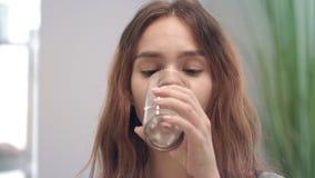 Mulher alegre que toma a cápsula e a água potável da vitamina do vidro na sala do banho video estoque