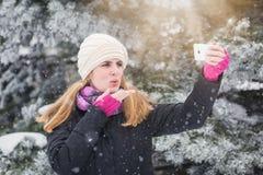 Mulher alegre que toma o autorretrato usando seu telefone esperto fotografia de stock