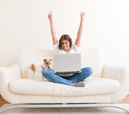 Mulher alegre que usa o portátil no sofá Imagem de Stock Royalty Free