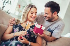 Mulher alegre surpreendente do homem novo com uma caixa de presente em h fotografia de stock royalty free