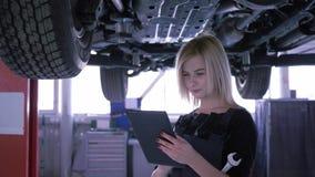 A mulher alegre verifica a condição técnica usando uma tabuleta digital sob o carro em um elevador hidráulico na estação do servi filme