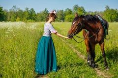 A mulher alimenta um cavalo com o animal do favorito das mãos imagens de stock royalty free