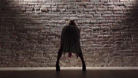 A mulher alta elegante nos saltos altos dança o twerk contra uma parede de tijolo Silhueta Movimento lento video estoque