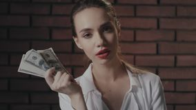 Mulher altiva que olha à câmera e que mostra a pilha do dinheiro à câmera na parede de tijolo video estoque