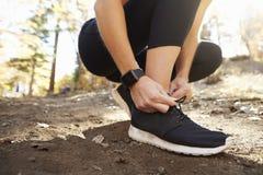 A mulher amarra a sapata dos esportes antes da corrida na floresta, fim acima do detalhe fotos de stock