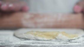 A mulher amassa a massa crua na cozinha Desenrola a massa com pino do rolo video estoque