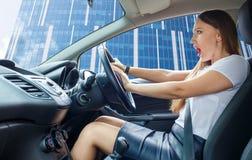 Mulher amedrontada jovens do motorista que toca o chifre Imagem de Stock