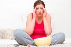 Mulher amedrontada que olha na tevê um filme Imagens de Stock Royalty Free
