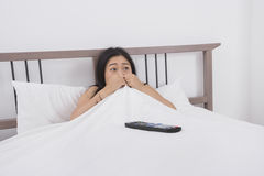 Mulher amedrontada que olha a tevê na cama Fotografia de Stock