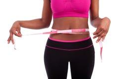 Mulher americana africana da aptidão que mede sua barriga Fotografia de Stock Royalty Free