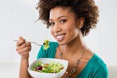 Mulher americana africana que come a salada