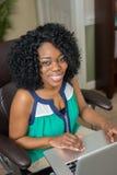 Mulher americana africana que usa o portátil Fotografia de Stock Royalty Free