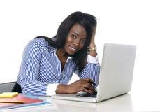 Mulher americana da afiliação étnica do africano negro que trabalha no portátil do computador no sorriso da mesa de escritório fe fotografia de stock royalty free