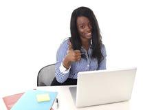 Mulher americana da afiliação étnica do africano negro que trabalha no portátil do computador no sorriso da mesa de escritório fe Imagens de Stock