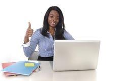 Mulher americana da afiliação étnica do africano negro que trabalha no portátil do computador no sorriso da mesa de escritório fe foto de stock