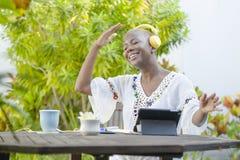 Mulher americana nova do africano negro bonito e feliz que aprecia fora no café que trabalha com a tabuleta digital que escuta wi foto de stock