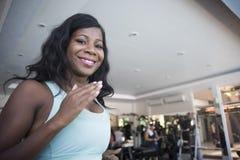 Mulher americana nova do africano negro feliz e atrativo no gym que corre no sorriso da máquina da escada rolante alegre e suado  fotos de stock