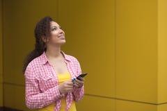 Mulher americana 20s com o cabelo encaracolado que guarda o telefone celular e que sorri na câmera isolada sobre o fundo amarelo imagens de stock