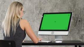 Mulher amigável nova do operador que fala e que trabalha no computador Exposição verde do modelo da tela filme