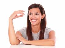 Mulher amigável que ri e que olha a sua direita Fotografia de Stock Royalty Free