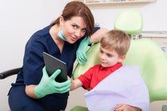 Mulher amigável e moderna do dentista boa com crianças Foto de Stock