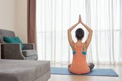 Mulher anônima que faz a ioga em casa fotos de stock royalty free