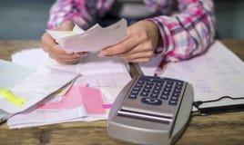 A mulher anônima sem cara entrega o trabalho com as contas do documento do banco e os originais financeiros que calculam despesas fotografia de stock royalty free