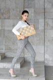 A mulher anda abaixo da rua com um tabuleiro de xadrez em suas mãos Imagens de Stock Royalty Free