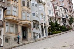 A mulher anda acima do declive íngreme em Nob Hill Street Fotografia de Stock Royalty Free