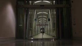 A mulher anda através das portas de vidro de deslizamento filme