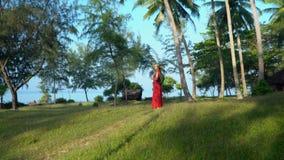 A mulher anda com uma trouxa Palmeiras altas na ilha Phu da ilha de Quoc a mulher em um vestido vermelho com a video estoque