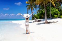 A mulher anda em uma praia tropical com chapéu branco foto de stock