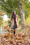 A mulher anda nas folhas de outono Imagem de Stock Royalty Free