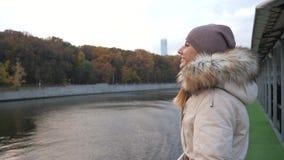 A mulher anda para flutuar a placa do barco e aprecia a vista do parque colorido no outono filme